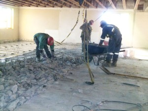 Workmen perform the difficult task of removing the Fellowship Room floor